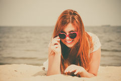 Redhaired happy girl in heart shaped sunglasses on beach. Royalty Free Stock Image