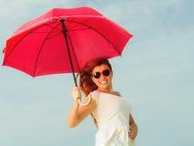 Redhaired Mädchen, das mit Regenschirm auf Strand springt Stockfotografie