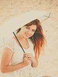 Redhaired Mädchen, das unter Regenschirm auf Strand sitzt Stockfoto