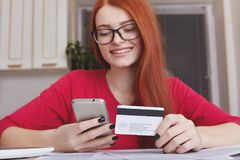 Redhaired pretty female model in eyewear holds smart phone and credit card, makes online purchase or shopping in internet store, h Stock Photos