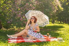 Redhaired pretty pinup woman in vintage summer dress and classic stockings with a seam in the back sits on a blanket on the grass. In the city Park, next to a royalty free stock image
