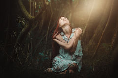 Redhaired woman alone in the woods. Romantic and surreal Stock Image