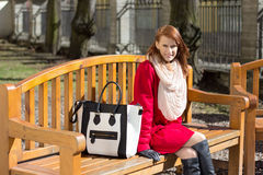 Redhaired woman crossing sitting on the bench in park Stock Photos
