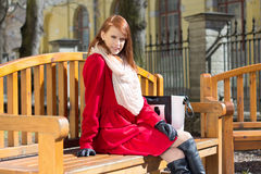 Redhaired woman crossing sitting on the bench Stock Image