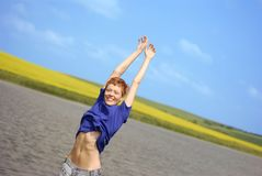 Redhaired woman jumping. Redhaired, happy woman jumping in a field Stock Photography