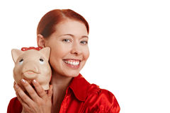 Redhaired woman with piggy bank Stock Photo