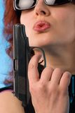 Redhaired woman with pistol. Red haired woman holding a pistol. fine-art close-up portrait on blue background Stock Images