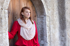 Redhaired woman posing in front of the old door Royalty Free Stock Photography