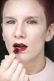Redhaired woman putting red lipstick on Stock Image