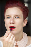 Redhaired woman putting red lipstick on Stock Photos