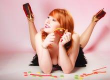 Redhairmeisje die het zoete suikergoed van de voedselgelei op roze houden Royalty-vrije Stock Afbeeldingen