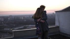 Redhead περιστροφές τύπων η φίλη του στη στέγη με έναν ορίζοντα εικονικής παράστασης πόλης και ηλιοβασιλέματος στο υπόβαθρο Ευτυχ απόθεμα βίντεο