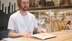 Redhead άτομο γενειάδων που έρχεται στον καφέ και που εργάζεται στο lap-top απόθεμα βίντεο