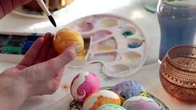 Redhead αυγά Πάσχας χρωμάτων κοριτσιών με μια βούρτσα στο κέικ επιτραπέζιου Πάσχας, αυγά, γλυκά, ανθοδέσμη των λουλουδιών φιλμ μικρού μήκους