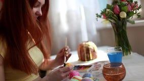 Redhead αυγά Πάσχας χρωμάτων κοριτσιών με μια βούρτσα στο κέικ επιτραπέζιου Πάσχας, αυγά, γλυκά, ανθοδέσμη των λουλουδιών απόθεμα βίντεο