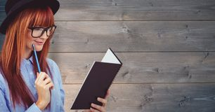 Redhead βιβλίο ανάγνωσης επιχειρηματιών πέρα από τον ξύλινο τοίχο στοκ φωτογραφία