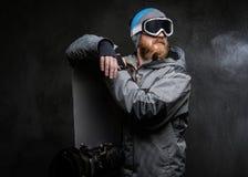 Redhead γενειοφόρο άτομο που φορά έναν πλήρη εξοπλισμό για ακραίο κλίνοντας σε ένα σνόουμπορντ και κοιτάζοντας μακριά, που απομον στοκ φωτογραφίες με δικαίωμα ελεύθερης χρήσης