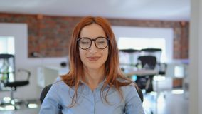 Redhead γυναίκα πορτρέτου που παρουσιάζει χαμόγελο στον εργασιακό χώρο απόθεμα βίντεο