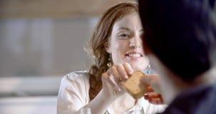 Redhead γυναίκα που περνά το ψωμί Τέσσερις ευτυχείς πραγματικοί ειλικρινείς φίλοι απολαμβάνουν το μεσημεριανό γεύμα ή το γεύμα μα απόθεμα βίντεο