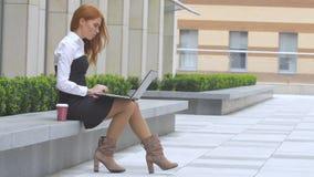Redhead γυναίκα που χρησιμοποιεί το lap-top με ένα φλιτζάνι του καφέ στο πεζούλι απόθεμα βίντεο