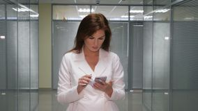 Redhead εκτελεστική εργασία με ένα κινητό τηλέφωνο στην αρχή απόθεμα βίντεο