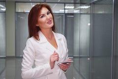 Redhead εκτελεστική εργασία με ένα κινητό τηλέφωνο στην αρχή στοκ εικόνες