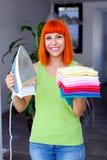 Redhead ενδύματα σιδερώματος γυναικών στο σπίτι Στοκ Φωτογραφία