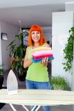 Redhead ενδύματα σιδερώματος γυναικών στο σπίτι Στοκ εικόνες με δικαίωμα ελεύθερης χρήσης