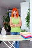 Redhead ενδύματα σιδερώματος γυναικών στο σπίτι Στοκ Φωτογραφίες