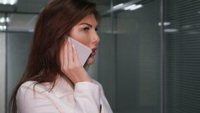 Redhead επιχειρηματίας που μιλά στο κινητό τηλέφωνο στο διάδρομο του γραφείου φιλμ μικρού μήκους