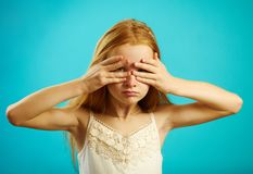 Redhead καλυμμένα κορίτσι μάτια με τα χέρια, που τιτιβίζουν μέσω των δάχτυλων στοκ φωτογραφία με δικαίωμα ελεύθερης χρήσης