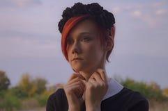 Redhead κορίτσι πορτρέτου με τα μαύρα λουλούδια κορωνών Στοκ Εικόνες