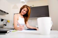 Redhead κορίτσι που εργάζεται στην κουζίνα στοκ φωτογραφίες