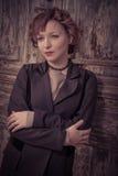Redhead κορίτσι ύφους που κλίνει την παλαιά ξύλινη πόρτα Στοκ φωτογραφία με δικαίωμα ελεύθερης χρήσης