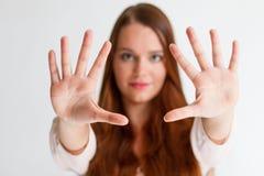 Redhead νέα γυναίκα που παρουσιάζει ανοικτά χέρια στο μέτωπο Στοκ Εικόνες