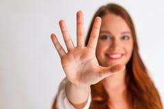 Redhead νέα γυναίκα που παρουσιάζει ανοικτά χέρια στο μέτωπο Στοκ Εικόνα