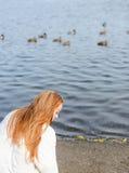 Redhead νέα γυναίκα που περπατά στο κοντινό νερό πάρκων φθινοπώρου στοκ φωτογραφία