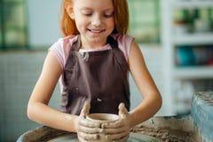 Redhead παιδί sculpts από το δοχείο αργίλου εργαστήριο στη διαμόρφωση σύμφωνα με τη ρόδα αγγειοπλαστών ` s Στοκ εικόνες με δικαίωμα ελεύθερης χρήσης
