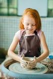 Redhead παιδί sculpts από το δοχείο αργίλου εργαστήριο στη διαμόρφωση σύμφωνα με τη ρόδα αγγειοπλαστών ` s Στοκ Φωτογραφίες
