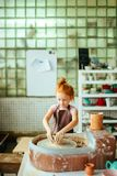 Redhead παιδί sculpts από το δοχείο αργίλου εργαστήριο στη διαμόρφωση σύμφωνα με τη ρόδα αγγειοπλαστών ` s Στοκ φωτογραφία με δικαίωμα ελεύθερης χρήσης