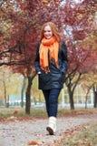 Redhead περίπατος κοριτσιών στη διάβαση στο πάρκο πόλεων, εποχή πτώσης Στοκ Εικόνα