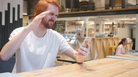 Redhead συνεδρίαση ατόμων γενειάδων στον καφέ που ανατρέπεται από την απώλεια εργασίας απόθεμα βίντεο