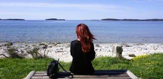 Redhead συνεδρίαση γυναικών μόνο στον πάγκο μπροστά από την ακτή στοκ φωτογραφία