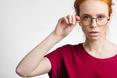 Redhead χαμογελώντας γυναίκα που φορά τα κόκκινα γυαλιά λαβής πουκάμισων στο άσπρο υπόβαθρο Στοκ φωτογραφίες με δικαίωμα ελεύθερης χρήσης