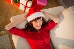 Redhead в шляпе santa ослабляя на кресле на рождестве Стоковое Фото