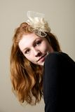 Redhead в cream fascinator рассматривая плечо Стоковые Изображения