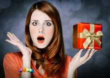 Redhead adult girl in coral shirt and gift box stock images