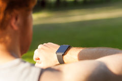 Redhead athlete, watching in smart wath or fitness tracker. Summer, morning, outdoor royalty free stock images
