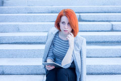 Redhead attractive business woman sitting outside on the stairs with tablet Stock Images