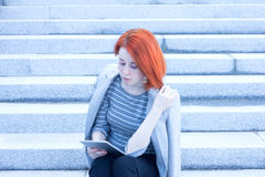 Redhead attractive business woman sitting outside on the stairs with tablet Royalty Free Stock Photography